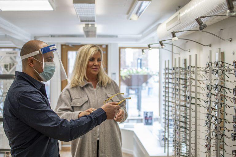 Kund till Fix-IT. Optiker visar glasögon för kund.